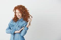 Bella ragazza allegra con capelli rossi sexy che pensa sognando le labbra mordaci sopra fondo bianco Fotografia Stock