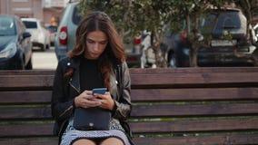 Bella ragazza allegra con uno smartphone che si siede in un parco su un banco su un adolescente di giorno soleggiato, concetto on video d archivio