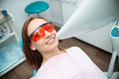 Bella, ragazza allegra nella sedia del dentista Trattamento dentale Clinica dentale immagine stock libera da diritti