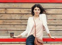 Bella ragazza alta con capelli lunghi castana in jeans che stanno sulle vecchie plance di legno con una tazza di caffè disponibil Immagini Stock Libere da Diritti