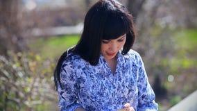 Bella ragazza asiatica che si siede nel parco su un banco e negli inizio facendo uso di uno smartphone archivi video