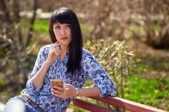 Bella ragazza asiatica che si siede sul banco in parco con il telefono a disposizione e che esamina la distanza Fotografia Stock