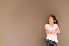 Bella ragazza asiatica che sta sul fondo grigio della parete, esaminante lo spazio della copia fotografia stock libera da diritti