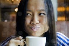 Bella ragazza asiatica con latte sugli orli Fotografia Stock