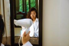 Bella ragazza asiatica nel bianco che asciuga i suoi capelli a casa fotografie stock