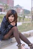 Bella ragazza asiatica pura che si siede dal lato della strada Immagini Stock