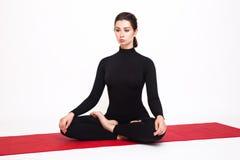 Bella ragazza atletica in un vestito nero che fa yoga Posa del loto di asana di Padmasana Isolato su priorità bassa bianca Fotografia Stock