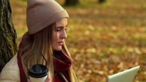 Bella ragazza, autunno nel parco, caffè bevente ed esaminare lo schermo del computer portatile video d archivio