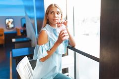 Bella ragazza, bevendo un cocktail, sedentesi in un caffè e fotografia stock