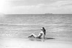 Bella ragazza in bikini che posa su una spiaggia abbandonata sabbia bianca, mare del turchese e una ragazza immagine stock libera da diritti