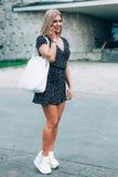 Bella ragazza bionda atletica con un'attrezzatura di estate che parla sul telefono Fotografie Stock
