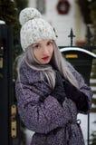 Bella ragazza bionda in cappello del pom del pom con le labbra di rosso di vino che cammina nella città Immagini Stock