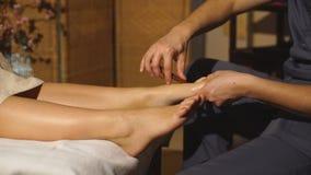 Bella ragazza bionda che fa massaggio del piede Massaggio terapeutico stock footage