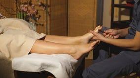 Bella ragazza bionda che fa massaggio del piede Massaggio terapeutico archivi video