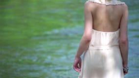 Bella ragazza bionda che indossa una corona del fiore e del vestito sulla testa che cammina verso il fiume Nuziale, giorno delle  archivi video
