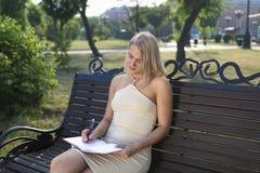 Bella ragazza bionda che si siede nel parco che prende giù le note importanti Immagine Stock Libera da Diritti