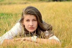 Bella ragazza bionda che si trova sull'erba asciutta Immagine Stock Libera da Diritti