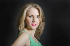 Bella ragazza bionda con gli occhi azzurri nel vestito verde o sorridente Fotografie Stock Libere da Diritti
