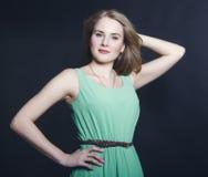 Bella ragazza bionda con gli occhi azzurri nel vestito verde o sorridente Immagine Stock