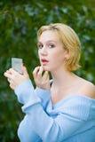 Bella ragazza bionda di Yong con gli occhi azzurri che mettono sul trucco Fotografia Stock