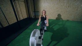 Bella ragazza bionda in ghette grige che fanno un esercizio nella palestra su un vogatore archivi video