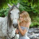 Bella ragazza bionda snella in vestito che abbraccia un cavallo grigio, outd immagini stock