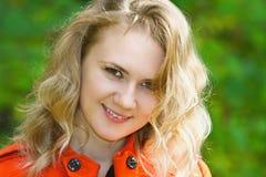 Bella ragazza bionda sorridente nel cappotto rosso Fotografie Stock