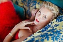 Bella ragazza bionda squisita elegante in un vestito rosso che si trova sopra fotografie stock libere da diritti