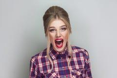Bella ragazza bionda stupita con la camicia a quadretti rosa, collecte fotografia stock libera da diritti