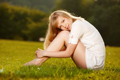 Bella ragazza bionda su un'erba fotografia stock libera da diritti