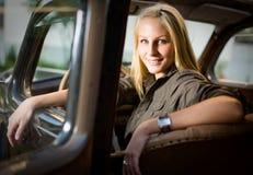 Bella ragazza bionda in un'automobile nera dell'annata. fotografia stock libera da diritti
