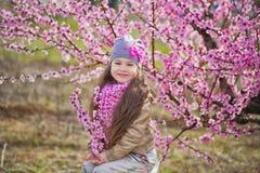Bella ragazza bionda vestita alla moda sveglia che sta su un campo di giovane pesco della molla con i fiori rosa Ragazza sorriden Fotografie Stock