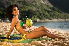 Bella ragazza brasiliana alla spiaggia con la noce di cocco Immagine Stock Libera da Diritti