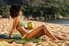 Bella ragazza brasiliana alla spiaggia con la noce di cocco Immagini Stock
