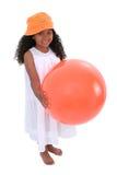 Bella ragazza in cappello della spiaggia e vestito da estate con la sfera arancione Immagini Stock Libere da Diritti