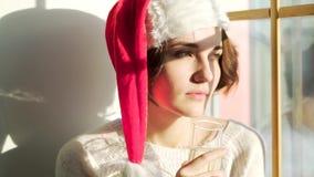 Bella ragazza in cappello di Santa Claus con un vetro di champagne che guarda dalla finestra, dal Christmass allegro e dal nuovo  archivi video