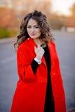 Bella ragazza in cappotto rosso che sta sulla strada fotografie stock