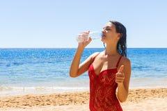 Bella ragazza castana in acqua potabile del costume da bagno rosso un giorno di vacanza fotografia stock