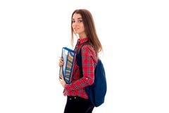 Bella ragazza castana alla moda dello studente con lo zaino blu e cartella per i taccuini in sue mani che esaminano la macchina f Fotografie Stock