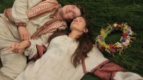 Bella ragazza castana in camicia ucraina tradizionale con la corona del fiore con il suo ragazzo che si trova al campo verde stock footage