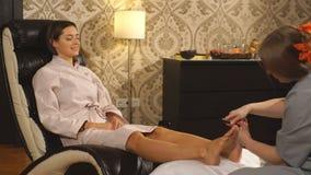 Bella ragazza castana che fa massaggio del piede Massaggio terapeutico archivi video