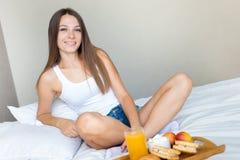 Bella ragazza castana che mangia una prima colazione sana a letto e sorridere fotografie stock libere da diritti