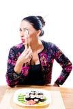 Bella ragazza castana con i bastoncini divertenti della tenuta delle labbra rosse ed i sushi dell'assaggio che esaminano macchina Fotografia Stock Libera da Diritti