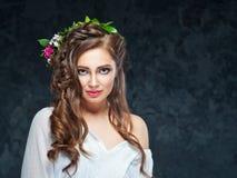 Bella ragazza castana con una composizione dei fiori Fotografia Stock