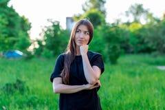 Bella ragazza castana di estate in un parco all'aperto con un gesto di mani che mostra uno sguardo premuroso Sogni di qualcosa fotografia stock