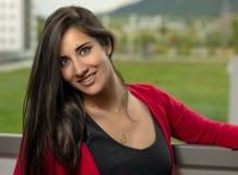 Bella ragazza castana e lunga dei capelli con un cardigan rosso che sorride alla macchina fotografica fotografia stock