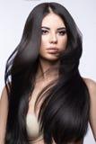 Bella ragazza castana nel movimento con i capelli perfettamente lisci e trucco classico Fronte di bellezza fotografia stock