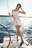 Bella ragazza castana sexy in yacht di viaggio di estate di trucco del vestito immagine stock