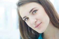 Bella ragazza castana sorridente che esamina macchina fotografica Immagine Stock Libera da Diritti