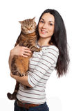 Bella ragazza castana sorridente ed il suo gatto dello zenzero sopra le sedere bianche Fotografie Stock